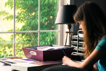 a girl writing at a desk