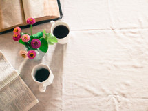 open Bible, flowers in a vase, and coffee mug on a tablecloth