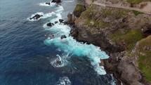 waves crashing into cliffs along a shoreline