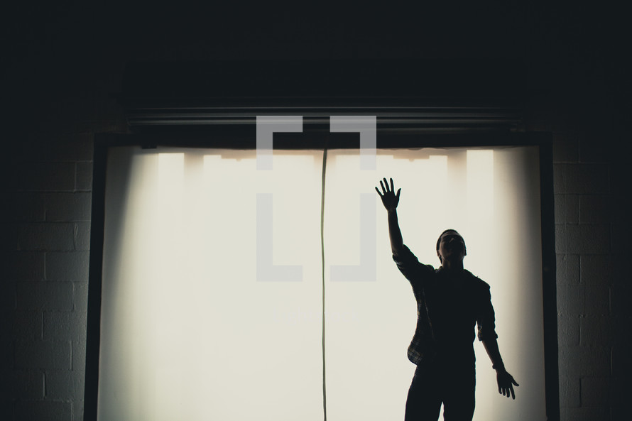 A man with hand raised, worshipping.