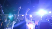 raised hands in worship during a youth rally