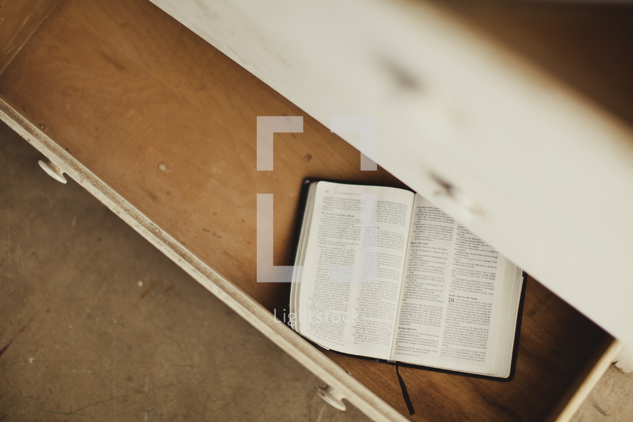 An open Bible sits in an open drawer