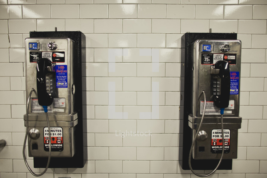 two modern pay phones on white tile wall