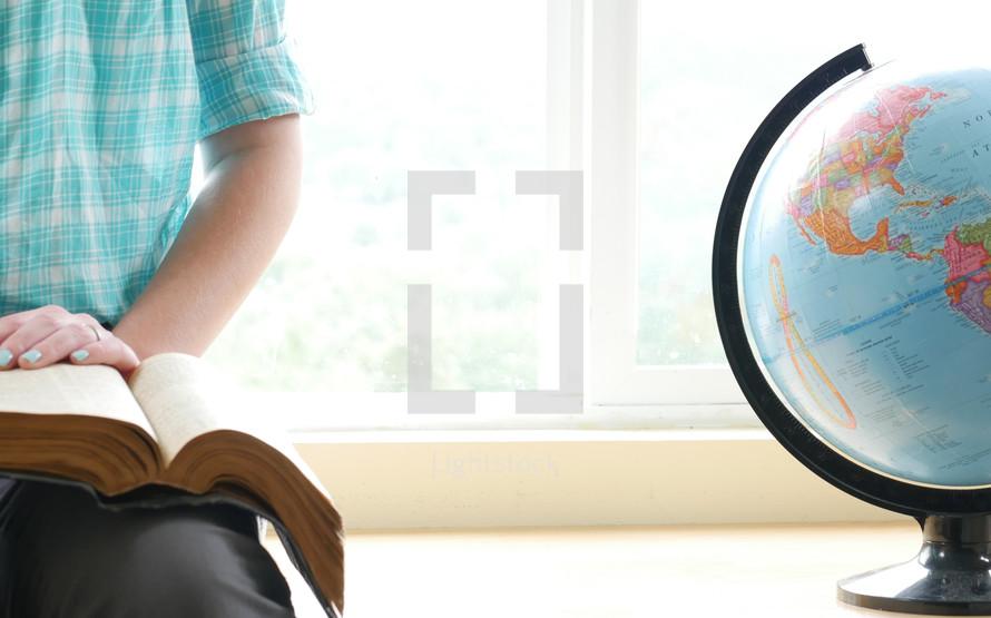 teen girl reading a Bible next to a globe