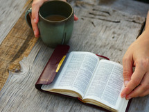 reading a pocket Bible and drinking coffee