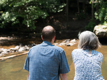 an elderly couple sitting and watching a river