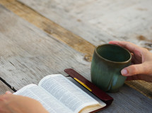 hand on a coffee mug while reading a pocket Bible