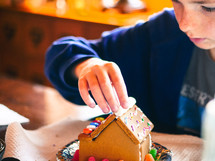 decorating a gingerbread house at Christmas