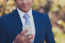 man in a suit checking his cellphone