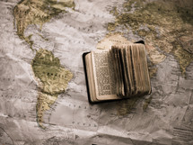 pages of a Bible and world map