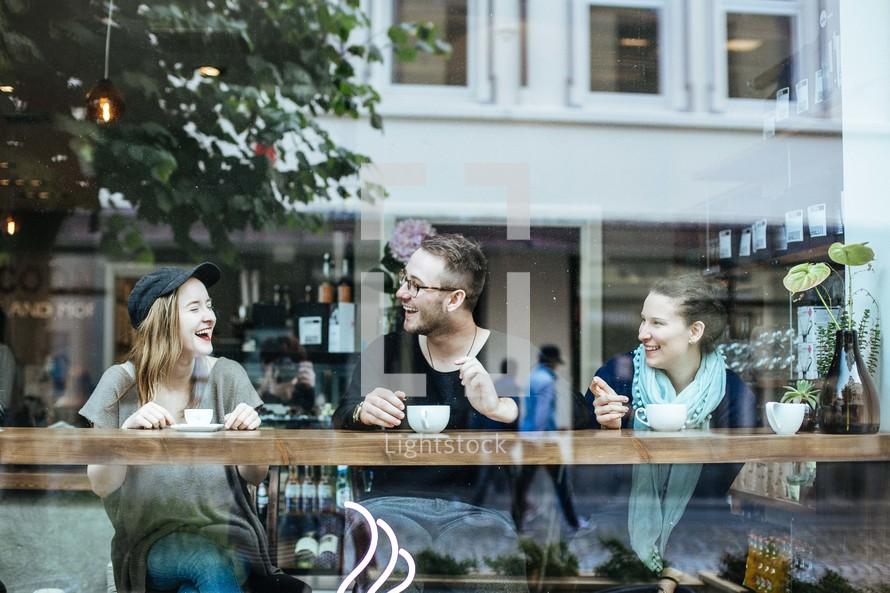 friends drinking coffee in a cafe window