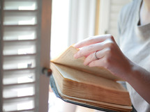woman reading a Bible at a window seat in a coffee shop