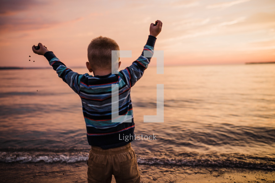 a boy playing with sand on a beach