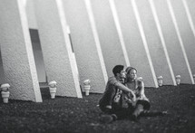 Couple sitting closely together on ground with modern building in background.