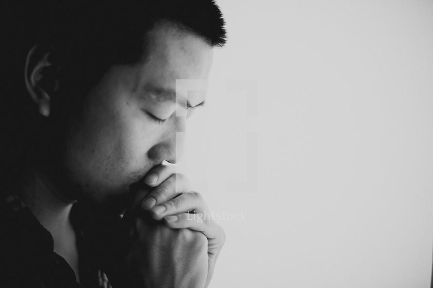 A young Asian man praying