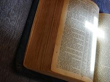 light in the shape of a cross on the pages of a Bible