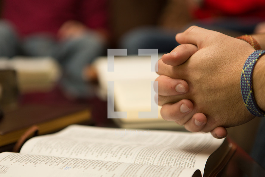 Hands clasped over bible open desk to Isaiah 55, The Compassion of the Lord.