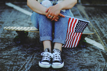 teen sitting on a skateboard holding an American flag