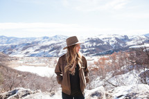 a woman in a hat posing on a mountain top