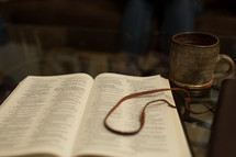 coffee cup in front of an opened Bible