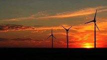 Wind turbines blowing at sunset.