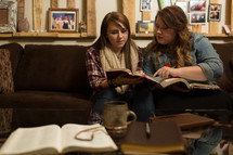women sitting on the couch reading Bibles at a Bible study