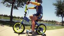 boy riding a bike with training wheels