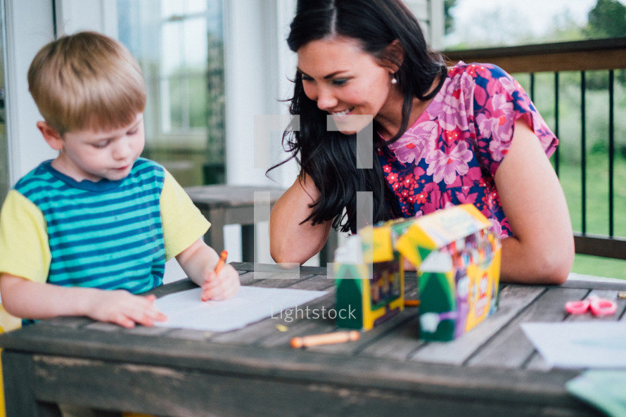 a mother and son coloring with crayons