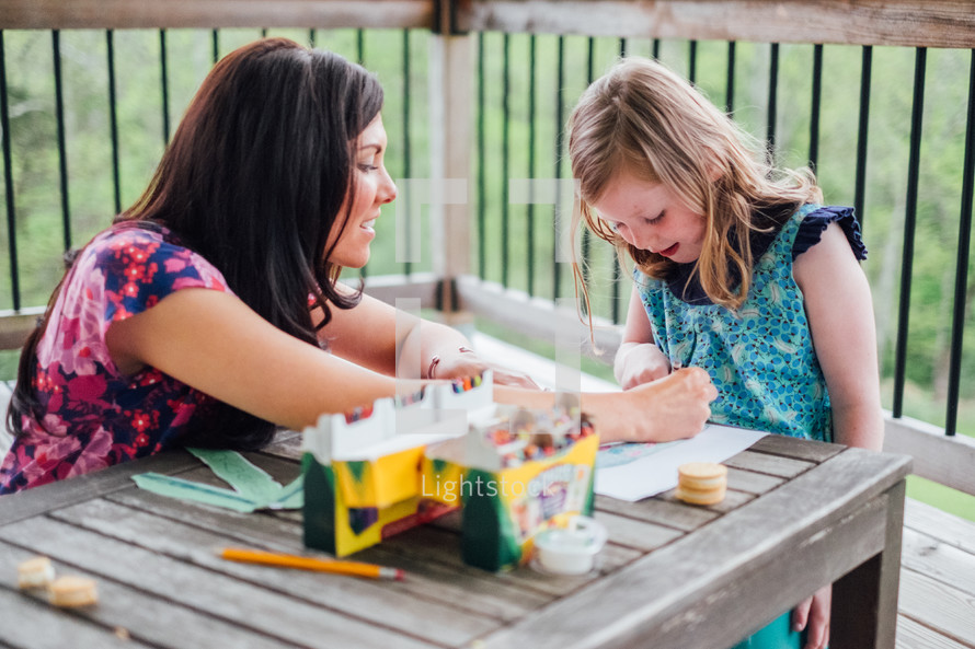 a mother and daughter coloring with crayons