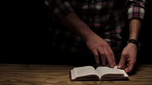 man standing turning the pages reading a Bible