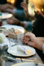 family holding hands in prayer at the dinner table