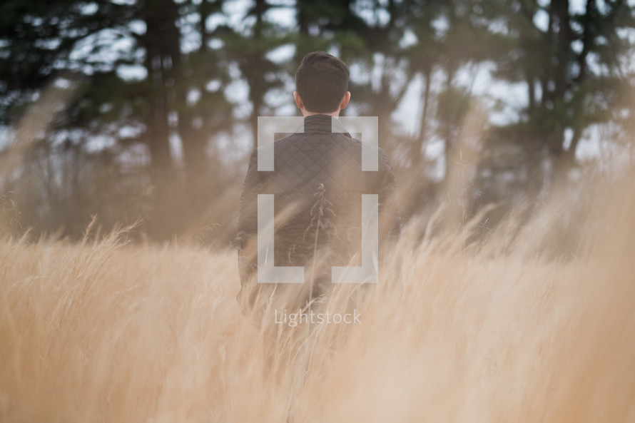 a man in a leather jacket walking through a field of tall grasses