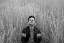 a man kneeling in tall grasses praying