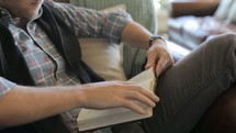 Man sitting on a couch relaxing and reading the Bible.