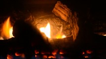Flames through the logs in a fireplace.