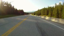 Timelapse of driving down a tree-lined mountain highway.