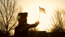 3 shots of a young child holding a waving American flag,  outdoors