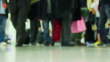 travelers carrying luggage and bags through an airport terminal