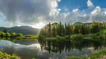 Timelapse of clouds moving across a pond with a mirror reflection of the trees and mountains.