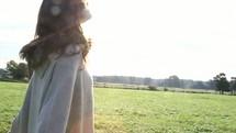 woman standing in a field under warm sunlight