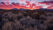 Timelapse of a fiery mountain sunset over a field of sagebrush.   This time-lapse was filmed near Mono Lake, California.