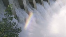 Water rushing through a hydro dam creating a rainbow.