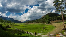 Clouds and shadows moving across a valley of pasture.