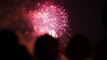 Fireworks bursting in the night sky and the silhouettes of children.