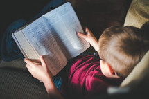 a kid reading a Bible on a couch