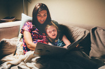 a mother reading to her daughter on the couch