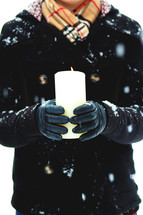 a woman holding a candle outdoors in a winter snow