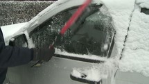 Cleaning snow off a car.