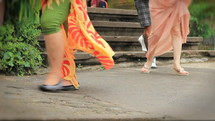A double speed shot of feet of people walking past shows a range of international people - locals and tourists from around the world.