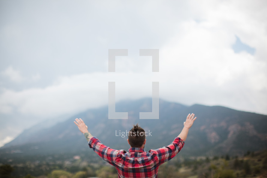 man in a plaid shirt with raised hands outdoors